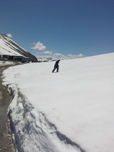Man Walking On Snow Covered Field Against Sky