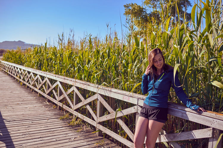 Young woman standing on footbridge by railing at field during sunny day