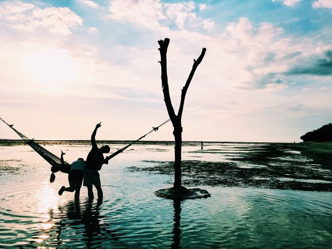 Water Silhouette Sky One Person Real People Nature Sea Men Outdoors Cloud - Sky Leisure Activity Holding Lifestyles Sunset Beauty In Nature Day Standing Scenics Horizon Over Water People