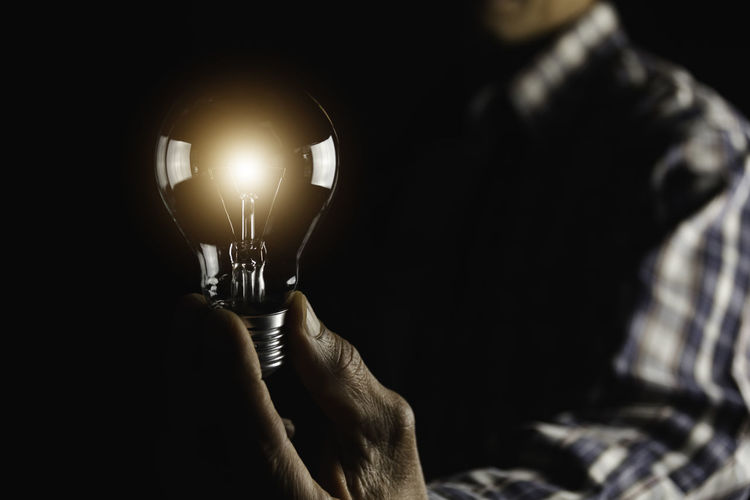 Close-up of hand holding illuminated light bulb