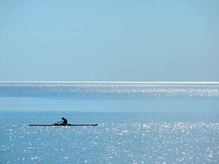 Silhouette person in boat at sea against clear blue sky on sunny day
