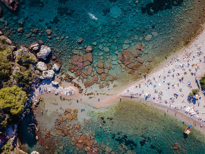 High angle view of crowd on rock by sea