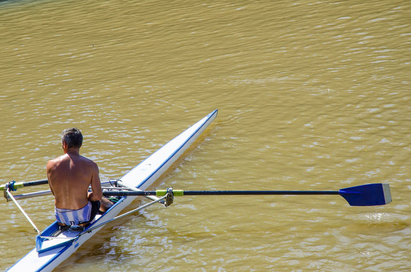 Shirtless man rowing boat on river