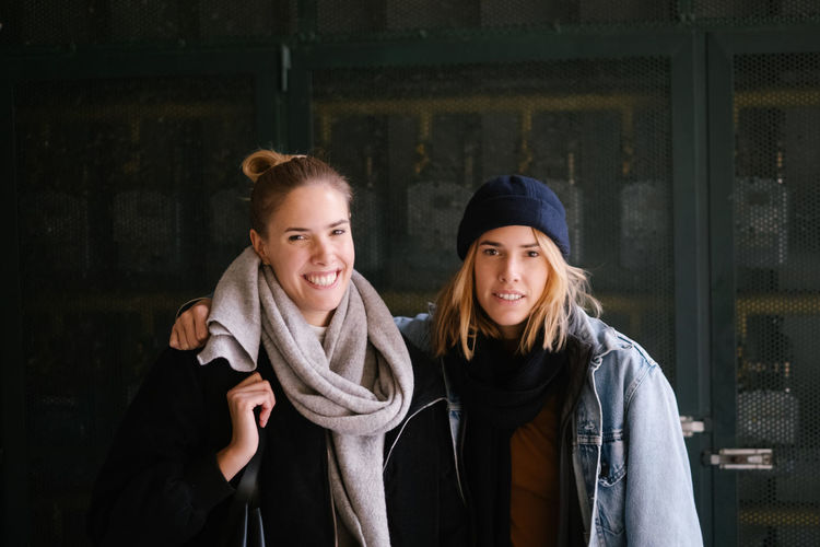 Portrait of smiling young women against wall