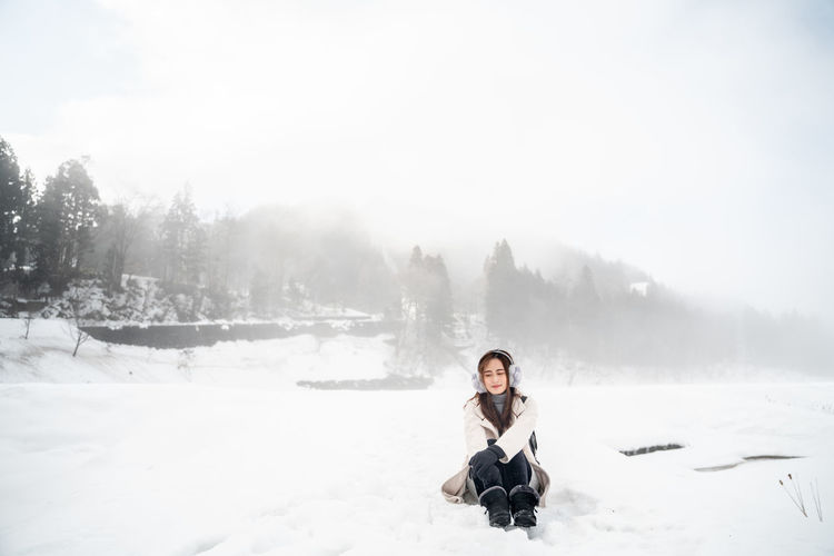 One Person Winter Cold Temperature Sitting Leisure Activity Young Adult Nature Beauty In Nature Snow Full Length Lifestyles Real People Non-urban Scene Day Scenics - Nature Looking At Camera Portrait Warm Clothing Outdoors Freedom