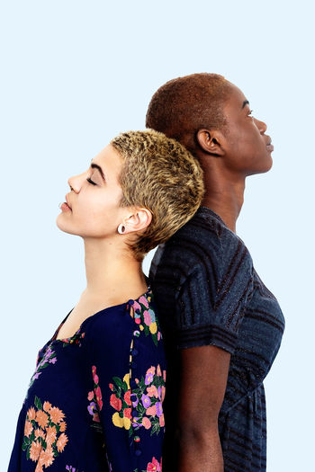 Lesbian couple standing back to back against white background