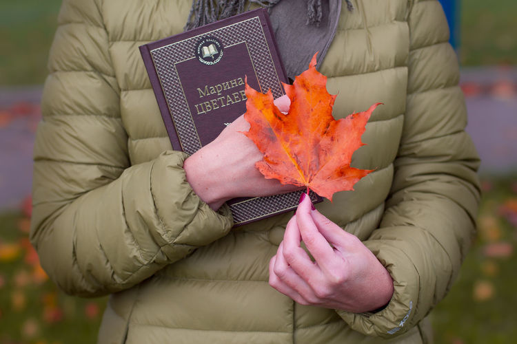 Midsection of person holding maple leaf during autumn