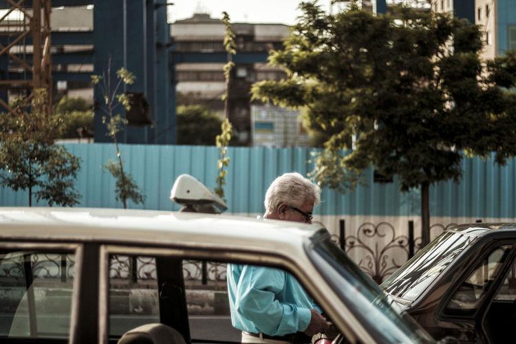 Man standing by car against buildings