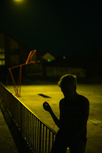 Silhouette woman smoking cigarette while sitting on railing at night