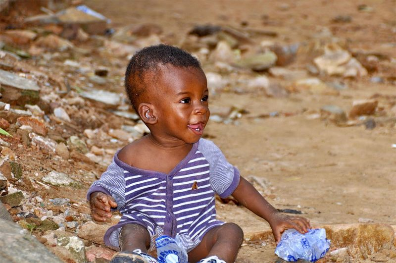 Smiling Baby Boy Sitting On Ground