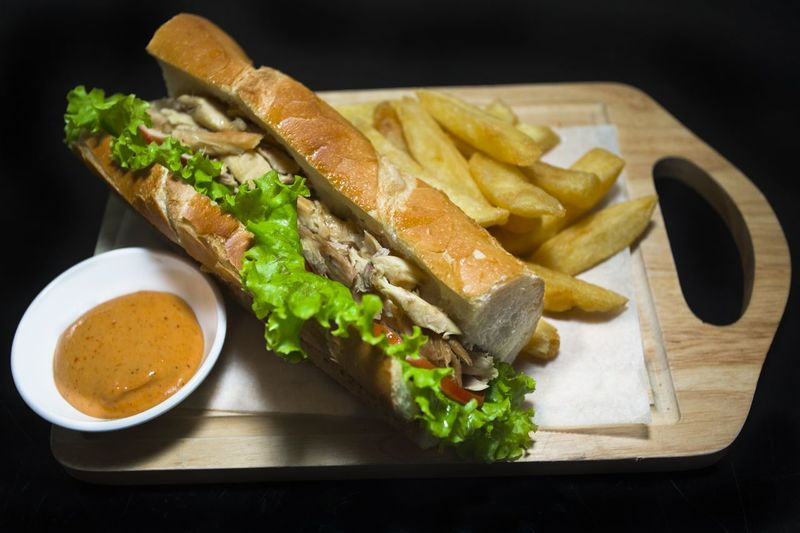 Sandwich with chicken and french fries on cutting board