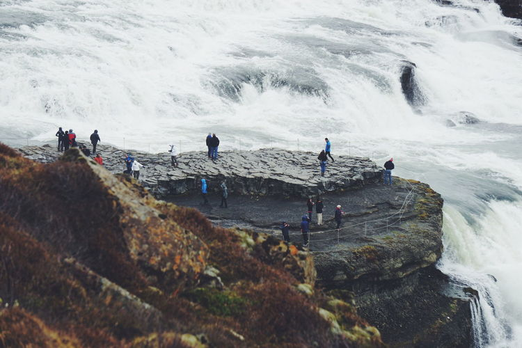High angle view of people standing on cliff by waterfall at gullfoss iceland
