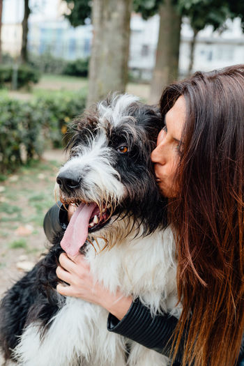 Beautiful woman embracing her dog at park Adult Adults Only Animal Body Part Bonding Close-up Day Dog Domestic Animals Friendship Headshot Human Body Part Human Hand Kiss Naples, Italy One Animal One Person Only Women Outdoors People Pet Owner Pets Protruding Terrier Yawning Young Adult