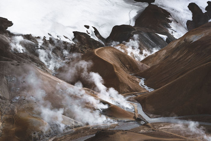 High angle view of steam emitting from volcanic mountains