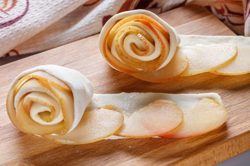 Preparation of buns from dough and apple slices. Apple Cooking Buns Close-up Cutting Board Day Dough Food Freshness Indoors  Napkin No People Preparation  Rolls Rosettes Sliced Table Towel Twist Wood - Material
