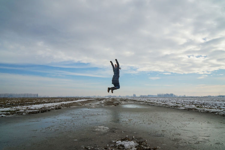 Woman with arms raised jumping at beach