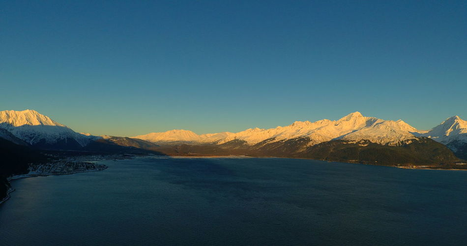 Scenic view of snowcapped mountains by sea against clear sky