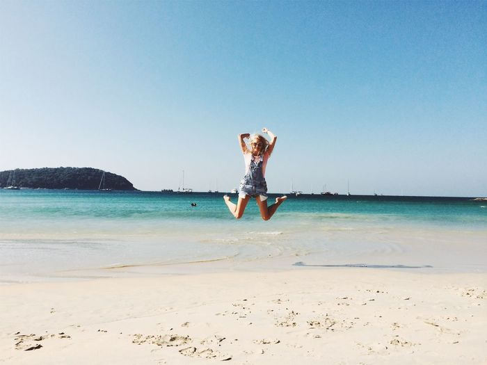 Full length of woman jumping at beach against clear sky
