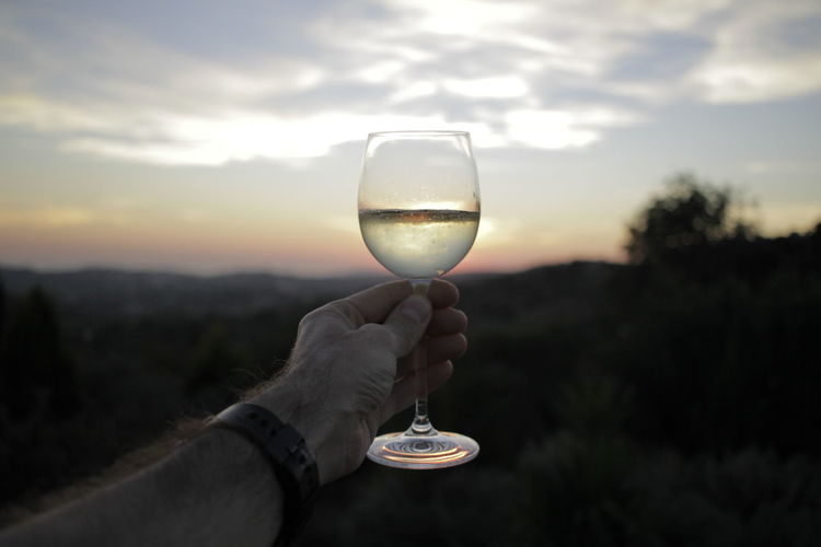 Close-Up Of Hand Holding Champagne In Glass Sunset