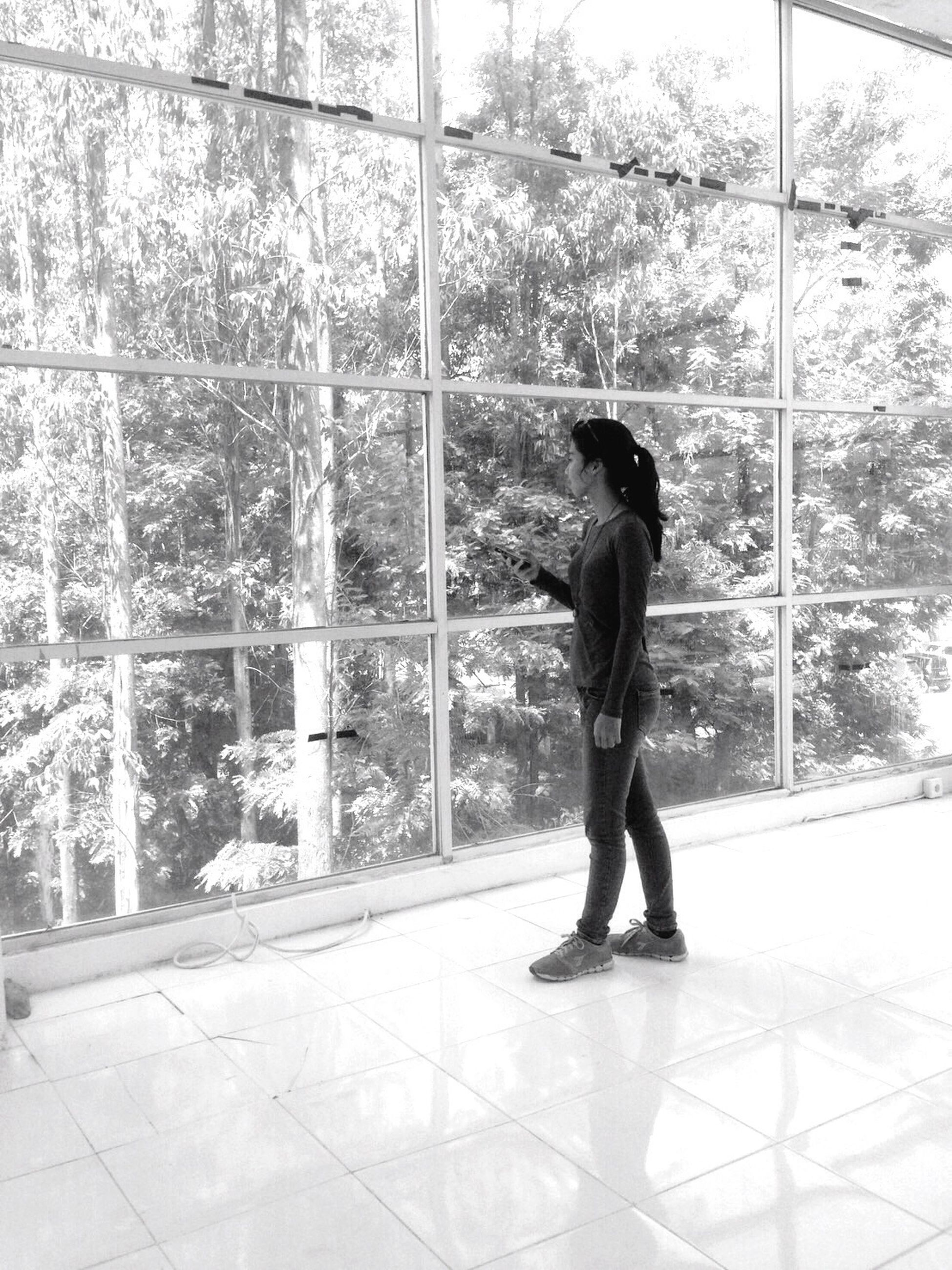indoors, full length, lifestyles, standing, window, glass - material, casual clothing, leisure activity, transparent, built structure, architecture, young adult, tiled floor, reflection, wall - building feature, person, day, young women