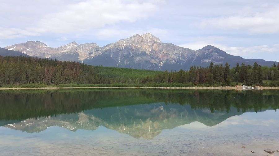 Reflection of trees and mountains in river against sky