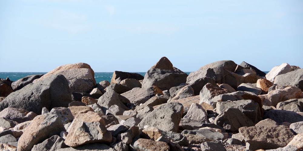 Rocks on beach against clear blue sky