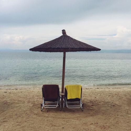 Chair on beach by sea against sky