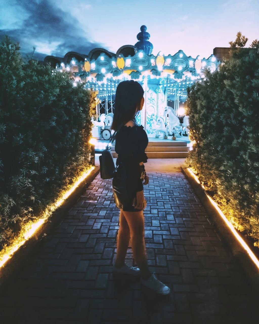 REAR VIEW OF WOMAN STANDING ON FOOTPATH AT NIGHT