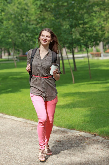 Young woman with a coffee cup running in an urban park. One Person Front View Smiling Full Length Young Adult Looking At Camera Real People Lifestyles Day Leisure Activity Beautiful Woman Running Coffee Cup Freshness Young Woman Woman Woman Running Morning Urban Park Park - Man Made Space Hurry Happiness Happy People