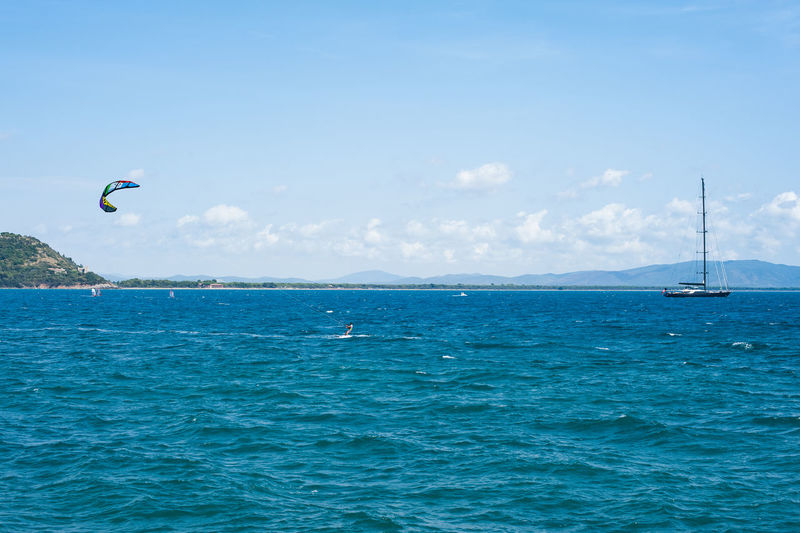 Distant view of person kiteboarding in sea against sky