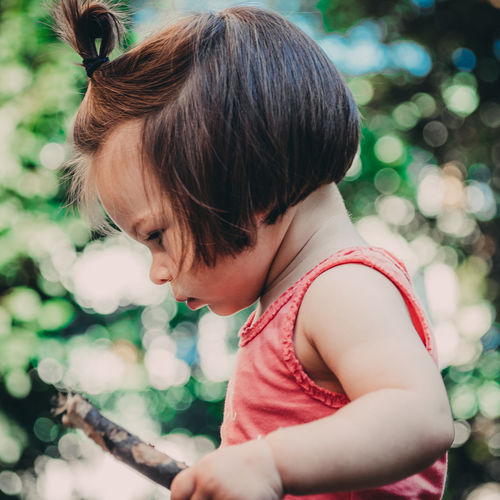 Side View Of Toddler Holding Stick