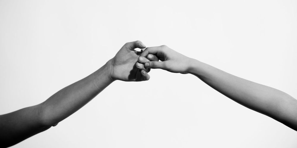 Cropped Image Of People Holding Hands Against White Background