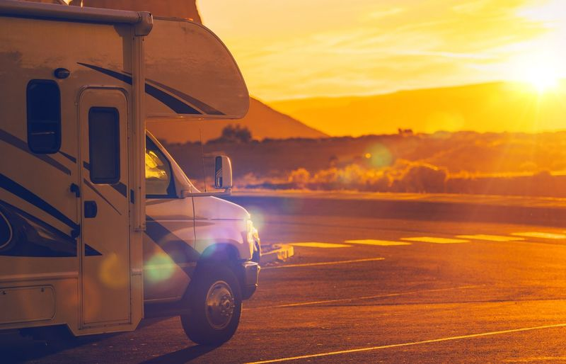 Travel trailer on road during sunset