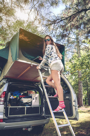 Woman Standing On Ladder While Removing Fabric Of Tent Over Car