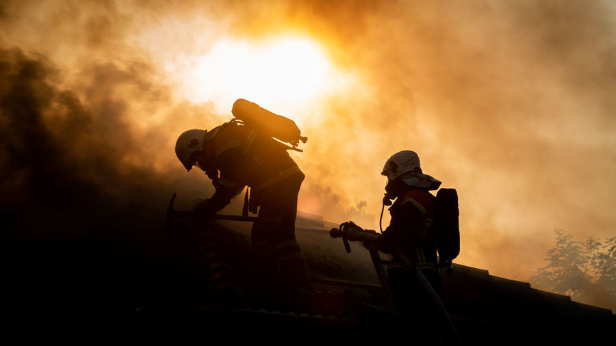 Silhouette Firefighters Against Sky During Sunset