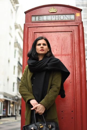 Beautiful woman looking away while standing against telephone booth