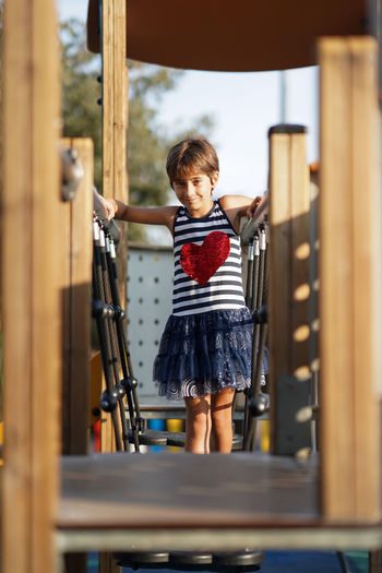 Portrait of girl standing on jungle gym in playground