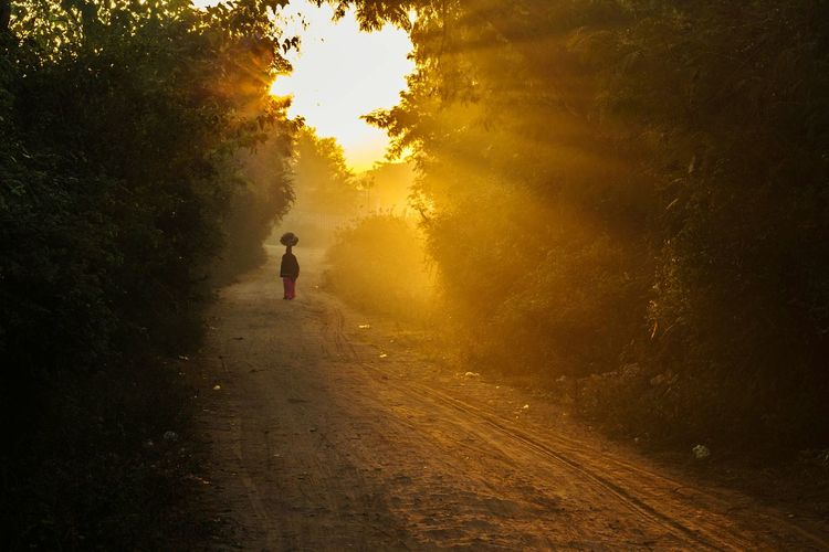 Rear view of woman carrying goods on head while walking on road during sunrise