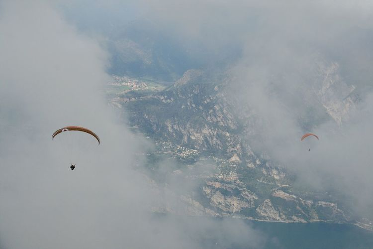 High Angle View Of Person Paragliding Over Mountains During Foggy Weather