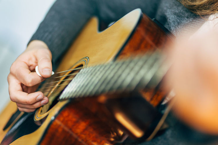 Acoustic Guitar Arts Culture And Entertainment Close-up Cropped Guitar Human Finger Lifestyles Music Musical Equipment Musical Instrument Musical Instrument String Part Of Person Playing Guitar Selective Focus Skill  Unrecognizable Person Work Tool