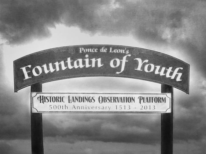 Black And White Photography Text Cloud - Sky Sky No People Outdoors Day Sign Signboard Signs Travel Places Magical Places Imaginary Foundation Fountain Of Youth Travel Destinations Wishful Thinking Places Of Apparition Wishful Wishful Thinking... Wooden Post Old Sign Text Words Of Wisdom... Funny Places
