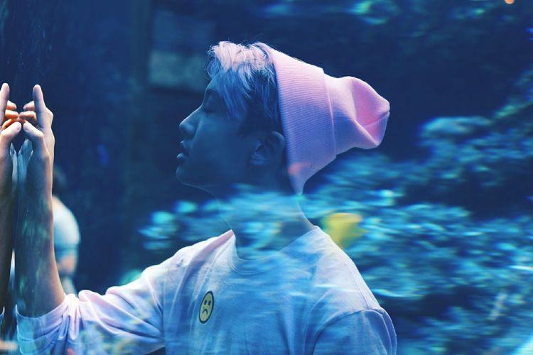 Side view of woman looking at aquarium