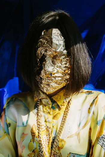 Young woman with face wrapped in golden foil