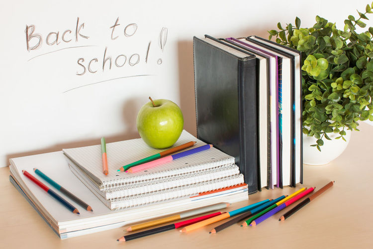 School supplies with apple and plant on table