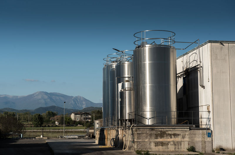Metallic silos at industry against clear blue sky