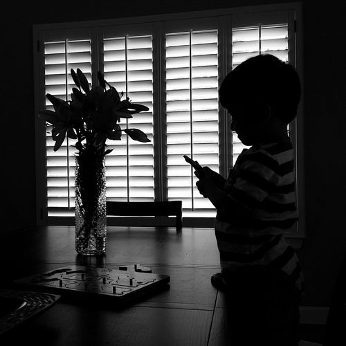 Side View Of Boy Standing By Puzzle On Table At Home