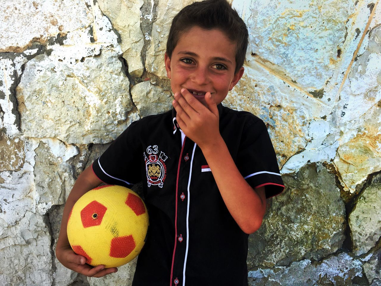 looking at camera, portrait, childhood, boys, one person, real people, soccer ball, leisure activity, holding, soccer, smiling, standing, playing, happiness, outdoors, day, one boy only, human hand, close-up, people