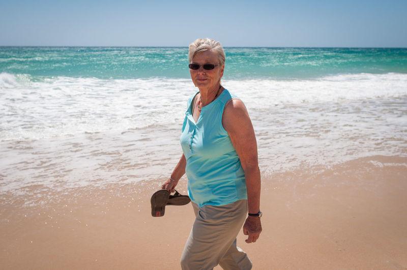 Senior Woman Walking On Beach