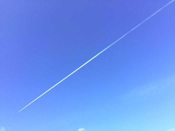 Low angle view of contrail at blue sky