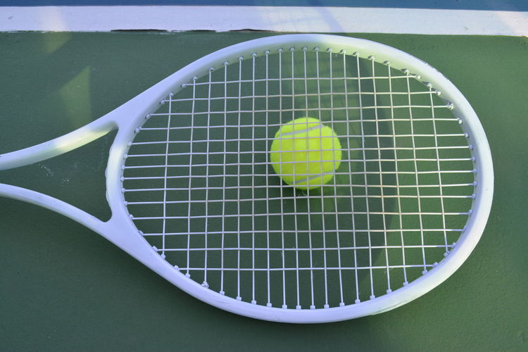 Directly above shot of ball on tennis racket at sports court